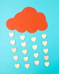 Rain of hearts. Concept of Valentine's Day from made of a blue background and a red cloud from which hearts fall.