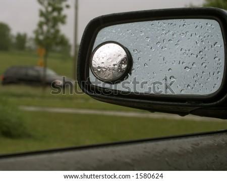 Rain on a car mirror.