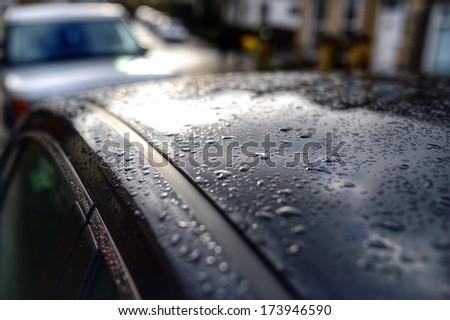 Rain on a car roof on a gloomy, dark winter morning.