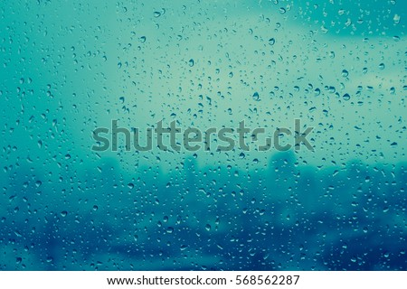 Rain on window texture rainy day or spring background. Green blue color background with sky cloud raindrops outside.