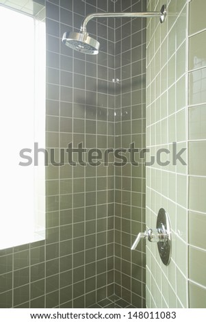 Rain shower head in green tiled bathroom