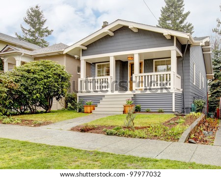 Rain-streaked bue grey small craftsman style house with white porch.