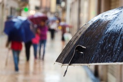 rain umbrella and walking people in the rainy city in the blurred background