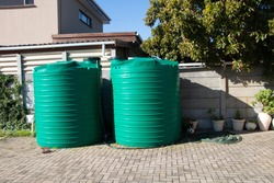 rain water catchment plastic tanks setup in backyard