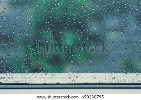 Rain / Water drop of rain on glass window in the rainy season and film tone with vintage