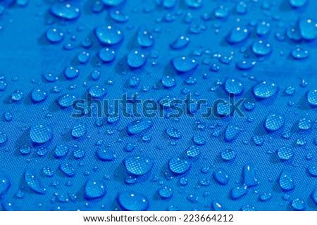 Rain Water droplets on blue fiber waterproof fabric
