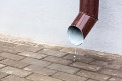 Rain water pipe with against grey wall