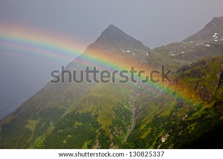 Rainbow arc against mountain ridge - stock photo