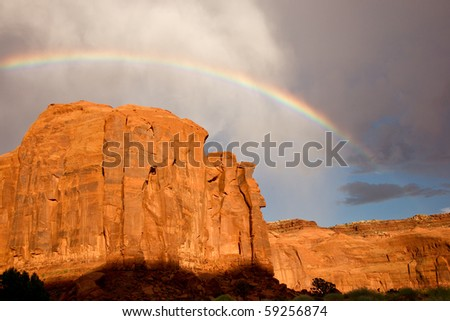 Rainbow arches above massive sandstone cliffs
