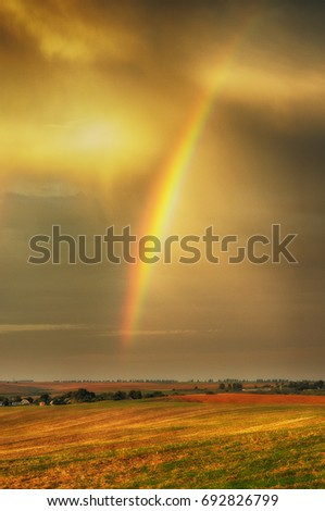 rainbow. Autumn dawn. Cloudy sky over the picturesque field #692826799