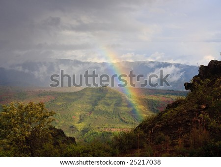 Rainbow behind craggy rocks in Waimea Canyon on Kauai