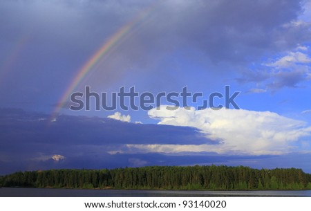 Rainbow breaks through storm clouds after the rain over lake in Minnesota, USA