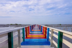 Rainbow bridge in Thailand. View of The colorful wood bridge extends into the sea under blue sky with white clouds at samut sakhon province,Thailand. Selective focus.