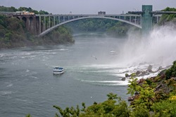 Rainbow Bridge over river and tourist boat under the American Falls, which are part of Niagara Falls