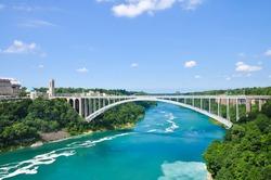 Rainbow Bridge over river with blue sky