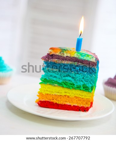 Rainbow cake decorated with birthday candle on the Birthday table