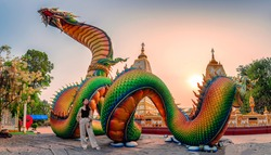 Rainbow carve serpent or colorful Thai Naga and asian woman standing in the sunset at Wat Phra That Nong Bua temple, Ubon Ratchathani