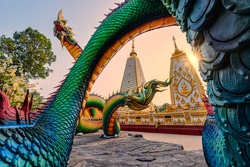 Rainbow carve serpent or colorful Thai Naga surrounding Sri Maha Pho Chedi stupa in the sunset at Wat Phra That Nong Bua, Ubon Ratchathani