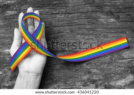 Rainbow color ribbon awareness on human hand with clipping path for Adrenocortical carcinoma and gay pride awareness ribbon #436041220