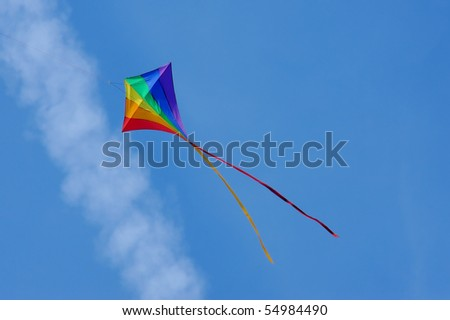 rainbow colored kite flying below an aircraft vapor trail - similar image with clear blue sky also available