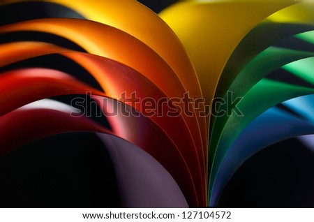 Rainbow colored paper on black background