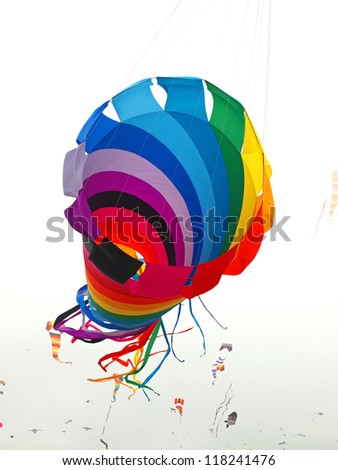 Rainbow Colored Tube Kite Flying on an Overcast Day at the Beach - stock photo