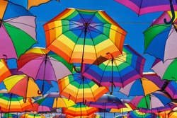 Rainbow Colored Umbrellas Hanging On The Background Of A Blue Sky