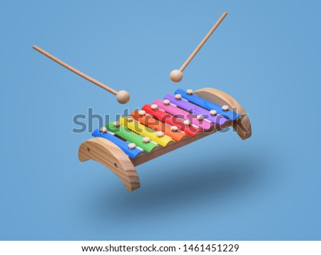 Rainbow colored wooden toy xylophone hovers in the air with two sticks. Isolated on light blue background stock photo
