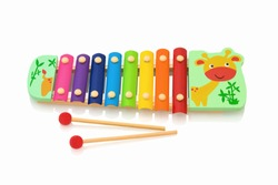Rainbow colored wooden toy xylophone isolated on white background with shadow reflection. Colorful wooden metallophone toy isolated on a white background. Xylophone with sticks.