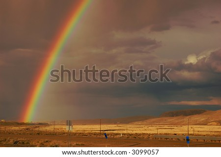 Rainbow emerging from the town of Elko, Nevada, in a rain storm over farmland and desert