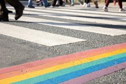 Rainbow flag, gay pride flag or LGBTQ pride flag painted on asphalt. City crosswalk decoration