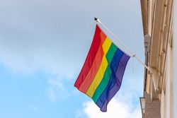 Rainbow flag hang outside the building and waving on the air in a sunny day and blue sky as background, Symbol of gay, lesbian, bisexual and transgender, LGBT social movements, Amsterdam, Netherlands.