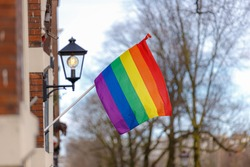 Rainbow flag hanging outside the building and waving on the air in a sunny day and blue sky, The Symbol of gay, lesbian, bisexual and transgender, LGBT social movements, Amsterdam.