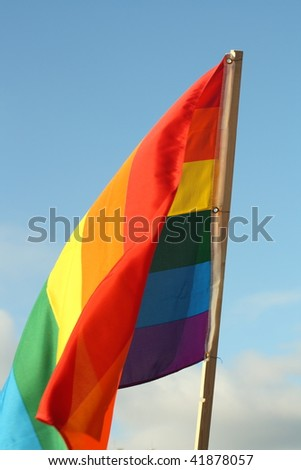 Rainbow flag on the sky background