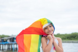 Rainbow flag symbol of love or LGBT pride concept.,Young girl show rainbow flag overhead. June pride month to celebrate pride festival, liberty right, freedom, proud to be equal and legal marriage.