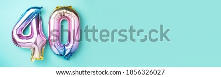 Rainbow foil balloon number, digit forty. Birthday greeting card with inscription 40. Anniversary concept. Top view. Colored numeral on blue background. Numerical digit, Celebration event, template. ストックフォト ©