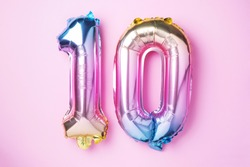 Rainbow foil balloon number, digit ten. Birthday greeting card with inscription 10. Anniversary concept. Top view. Colored numeral on pink background. Numerical digit, Celebration event, template.