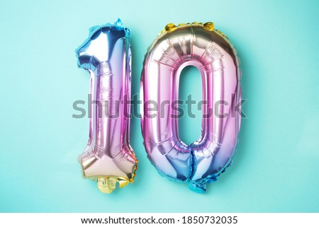 Rainbow foil balloon number, digit ten. Birthday greeting card with inscription 10. Anniversary concept. Top view. Colored numeral on blue background. Numerical digit, Celebration event, template. ストックフォト ©