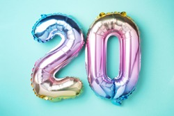 Rainbow foil balloon number, digit twenty. Birthday greeting card with inscription 20. Anniversary concept. Top view. Colored numeral on blue background. Numerical digit, Celebration event, template.