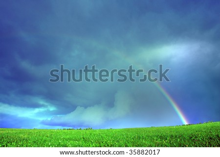 Rainbow,green field and blue sky.