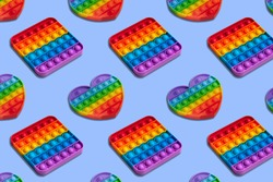 Rainbow heart and square shape isometric pattern of silicon toy for kids. Pop it fidget toy on pastel background. Simle dimple toy on blue pastel background.