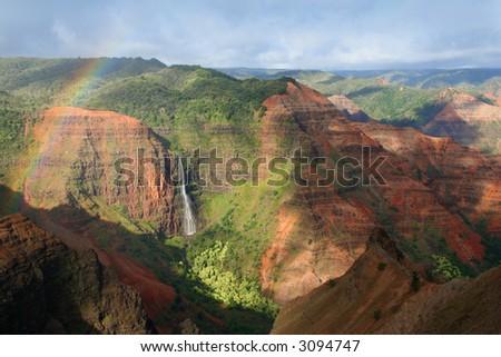 Rainbow hovers over a waterfall at Waimea Canyon in Hawaii