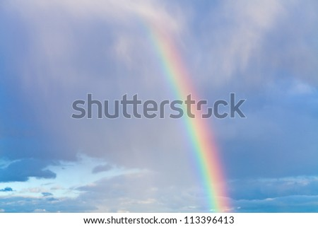 rainbow in autumn blue cloudy sky