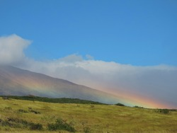 rainbow in front of a volcanic mountain