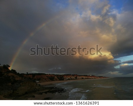 rainbow in moody clouds #1361626391