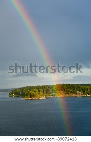 rainbow in rain during sunshine in Baltic sea