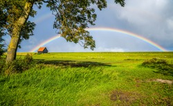 Rainbow in sky clouds over rural house lawn summer field country landscape