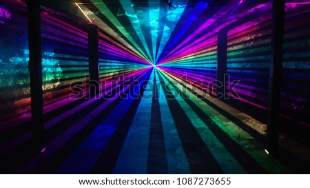 Rainbow laser beams shine from a central point past four silhouetted columns on an otherwise empty background. Music festival / nightclub / heaven  #1087273655