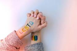 Rainbow LGBTQ flag painted on hand. Support for lgbt community. Honour of pride month. Connecting people, touching hands. Multi colored hands art creativity, discrimination.