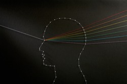 Rainbow mind concept. Network of pins and threads in the shape of a ray of light going through a persons head symbolising that the mind is a prism and thoughts are a refraction process.